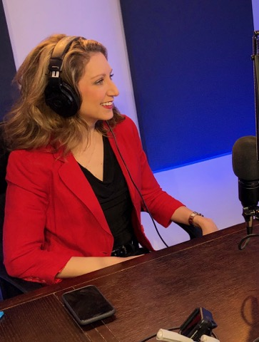 An image of a woman wearing headphones dressed with black shirt and wearing red blazer
